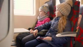 坐在火车的乘客座位和看对窗口的旅行的女孩少年 影视素材