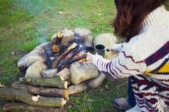 坐在火附近的人们 免版税库存照片