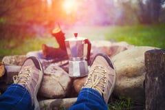 坐在火附近的人们 库存照片