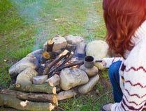 坐在火附近的人们 库存图片