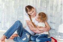 坐在灰色墙壁的两个女孩 免版税库存照片
