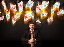 坐在灼烧的税和票据纸下的沮丧的商人 免版税库存照片