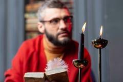 坐在灼烧的蜡烛附近和读古老书的有胡子的占卜者 免版税库存照片