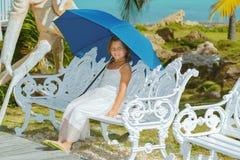 坐在热带庭院里的快乐的小女孩 图库摄影