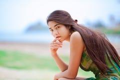 坐在热带海滩的美丽的两种人种的青少年的女孩,认为 库存图片