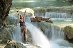 坐在热带瀑布的妇女 免版税库存照片