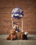 坐在热空气气球的试验孩子外面 免版税库存照片