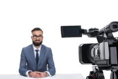 坐在照相机前面的男性新闻广播员选择聚焦, 免版税图库摄影