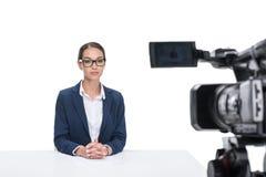 坐在照相机前面的衣服的女性新闻广播员, 免版税库存图片
