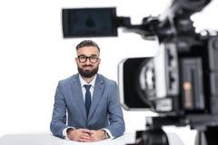 坐在照相机前面的衣服的微笑的男性新闻广播员, 图库摄影