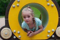 坐在爬行管的女孩 图库摄影