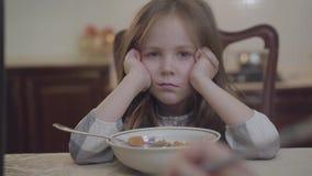 坐在父母前面的画象小不快乐的女孩的关闭被扶植她的看在照相机的头 r 股票视频