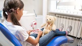 坐在牙医椅子和使用与她的在医生和患者的玩具熊的逗人喜爱的女孩的特写镜头图象 库存图片