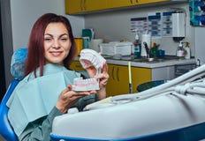 坐在牙医椅子和拿着假牙的年轻红头发人妇女在牙医办公室 库存照片
