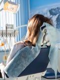 坐在牙齿椅子的年轻女性耐心参观的牙医办公室后面看法  诊所口腔医学 库存图片