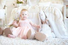 坐在玩具兔子之间的小哭泣的女孩临近床 免版税库存图片