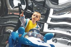 坐在玩具汽车的小男孩显示手指 免版税库存照片