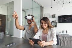 坐在现代公寓妇女用途数字式片剂白人穿戴3d Vr玻璃的表上的年轻夫妇 库存照片