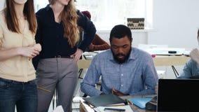 坐在现代办公室桌上的被注重的和生气非洲男性雇员繁忙与文书工作在两个女性同事附近 股票视频