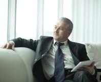 坐在现代办公室的负责任的商人 人们和技术 免版税库存照片