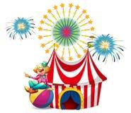 坐在球上的小丑在狂欢节 免版税库存图片