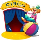 坐在球顶部的小丑指向马戏房子 免版税库存照片