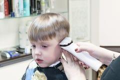 坐在理发店的男孩 它切开她的美发师 库存图片