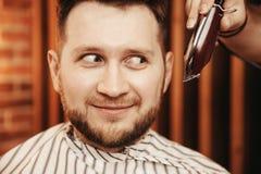 坐在理发椅的惊奇的人,为头发切口做准备 概念理发店 免版税库存照片