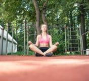 坐在瑜伽位置的少妇 免版税库存图片