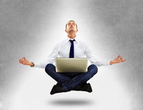 坐在瑜伽位置的生意人 免版税图库摄影