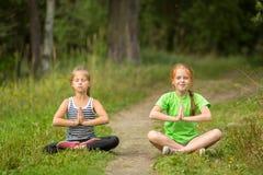 坐在瑜伽凝思的两个小女孩户外 免版税库存照片