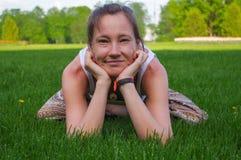 坐在瑜伽姿势凝思的少妇户外 图库摄影