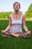 坐在瑜伽姿势凝思的少妇户外 免版税库存照片
