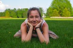 坐在瑜伽姿势凝思的少妇户外 库存图片