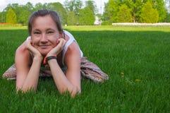 坐在瑜伽姿势凝思的少妇户外 免版税图库摄影