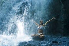 坐在瑜伽姿势的岩石的可爱的妇女精神放松平静和凝思的在惊人的美丽的瀑布和 库存照片