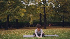 坐在瑜伽姿势的席子享受新鲜空气、和平和放松的灵活的小姐 都市的健康生活方式 股票视频