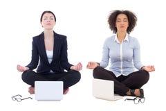 坐在瑜伽的两个女商人摆在与被隔绝的膝上型计算机  免版税库存照片