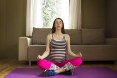 坐在瑜伽的莲花坐的美丽的年轻孕妇 免版税库存图片