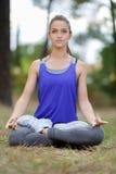 坐在瑜伽莲花姿势凝思的少妇户外 免版税库存照片