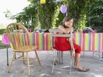 坐在生日聚会表上的女孩 库存照片