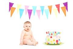 坐在生日蛋糕和党旗子旁边的逗人喜爱的男婴 免版税库存照片