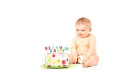 坐在生日蛋糕旁边的尿布的一个9个月婴孩 库存图片