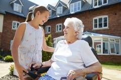 坐在电动轮椅的孙女参观的祖母在养老院 免版税库存图片