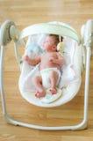 坐在电子摇摆的逗人喜爱的新出生的男婴 库存图片