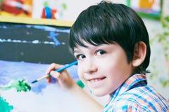 坐在画架前面的年轻男孩绘鱼,拿着刷子手中和调查kamera微笑 男孩是 免版税图库摄影