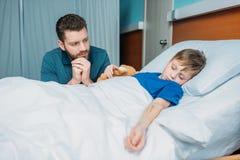 坐在病的儿子附近的沉思爸爸画象 免版税图库摄影