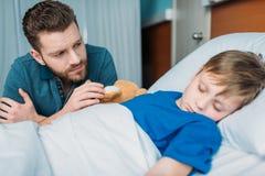 坐在病的儿子附近的生气爸爸在医院病床上 免版税库存照片
