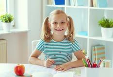 坐在白色桌上的逗人喜爱的学校女孩画象在轻的教室 免版税库存图片