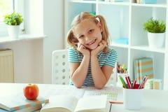 坐在白色桌上的逗人喜爱的学校女孩画象在轻的教室 免版税库存照片